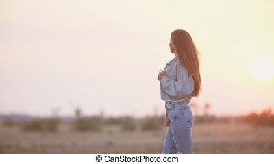girl in jeans clothes against the setting sun - beautiful...