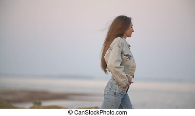 girl in jeans clothes on a background of the sea - beautiful...