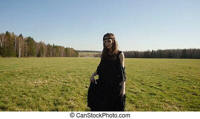 Beautiful girl in long black dress walks on field