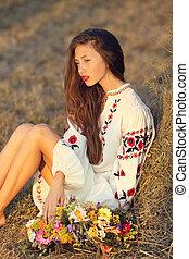 Beautiful girl in meadow in national suite