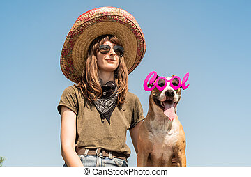 Beautiful girl in mexican hat dressed up as bandit of gangster with dog in cool sunglasses. Female person in sombrero hat and bandana posing with puppy as mexico festive symbol or for halloween