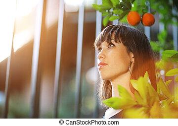 Beautiful girl in orange tree garden