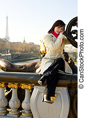 Beautiful girl in Paris sitting on the balustrade of Pont Alexandre III