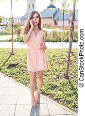 beautiful girl in pink dress, makes phone calls, summer in city park, holds smartphone, listens to audio message on Internet, online application in social networks talking.