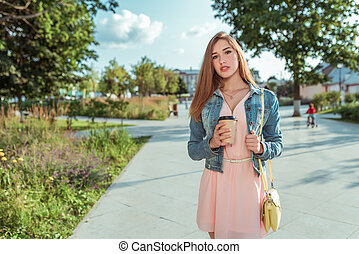 beautiful girl in pink dress, stands in summer in city park, holds cup of coffee tea, bag over her shoulder, emotions pleasure. Free space for text.