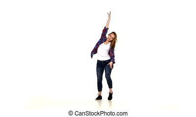 Beautiful girl in plaid shirt dancing lady style and turns on white background