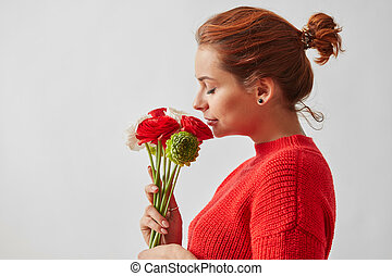 Beautiful girl in profile, smelling flowers of a rose on a white background.