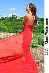 girl in red dress against urban landscape