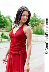 Beautiful girl in red dress posing on the street