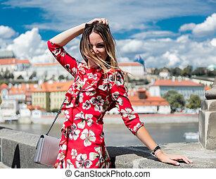 Beautiful girl in red dress travel in Prague