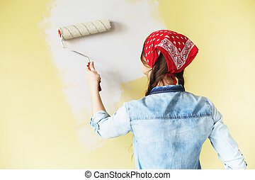 Beautiful girl in red Headband painting the wall with paint roller. Portrait of a young beautiful woman painting wall