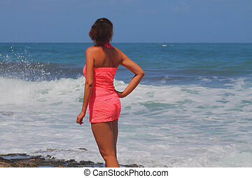 beautiful girl in red looks at the sea