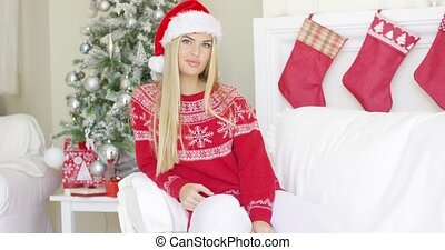Beautiful girl in Santa Claus hat in her living room