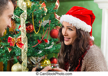 Beautiful girl in Santa hat looking at guy on Christmas