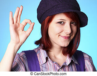 Beautiful girl in shirt and violet cap show OK
