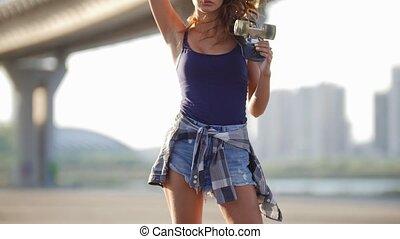 Beautiful girl in short shorts, a t-shirt and a plaid shirt...