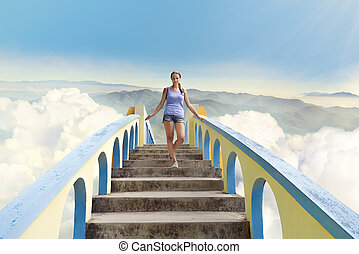 Beautiful girl in shorts walking on the bridge above the clouds on a background of mountains