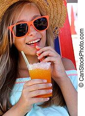 Beautiful girl in sunglasses and slush on beach