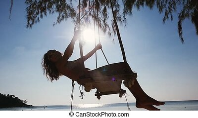 Beautiful girl in sunglasses relax on the swing at the beach. Woman in a bikini of the tropical ocean. slow motion. 1920x1080