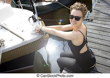 Beautiful girl in sunglasses sitting on a pier near the boat in the sunlight