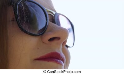 Beautiful girl in sunglasses with red lips enjoying the sunlight on nature.