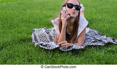 Beautiful girl in sunglasses with smartphone lies on the grass.