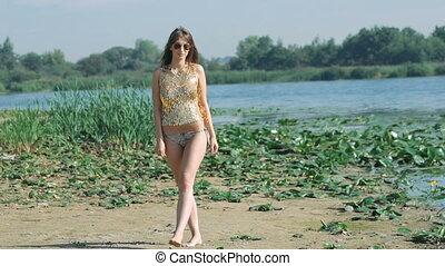 Beautiful girl in swimdress posing near the sea. Slowly