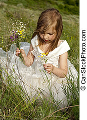 Beautiful girl in the clothes of bride on the field with the field flowers