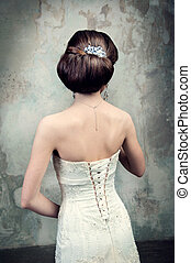 beautiful girl in the dress of the bride from the back