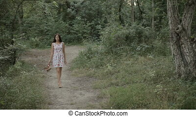 Beautiful girl in the dress walking along a path in the woods