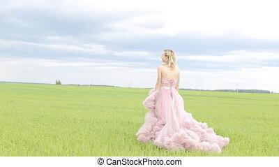 Beautiful girl in the dress walks in the field