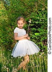 Beautiful girl in the forest with dandelion