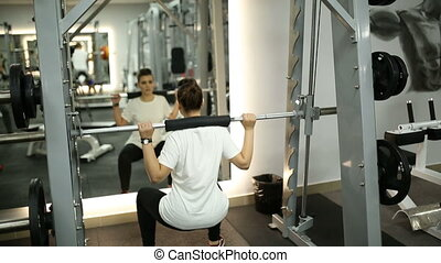 Beautiful girl in the gym crouches with a barbell