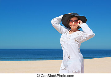 Beautiful girl in the hat on the beach.