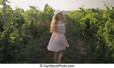 Beautiful girl in the hat walks through the vineyard