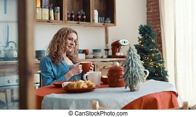 Beautiful girl in the kitchen with cup of coffee in the morning before Christmas