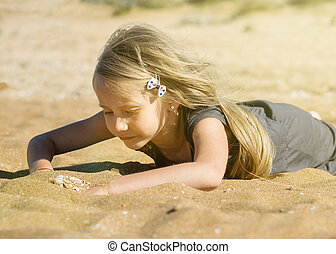 Beautiful girl in the rays of the sun looked closely at the sea sand.