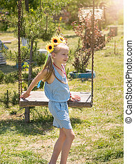 Beautiful girl in the rays of the sun with the decoration of flowers on her head on the old swing. The attraction of the past.