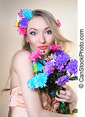 Beautiful girl in the studio with a bunch of flowers