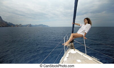 Beautiful girl in the swimsuit sits on the bow of the yacht and sunbaths in the sea