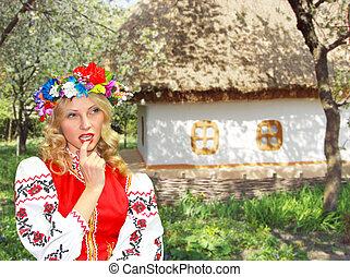 Beautiful girl in the Ukrainian national costume in garden near the house