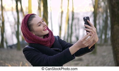Beautiful girl in the woods makes selfie