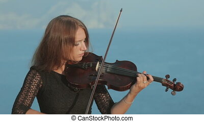 Beautiful girl in tracery dress playing the violin standing on a rock by sea