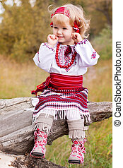 Beautiful girl in ukrainian costume sitting on a log