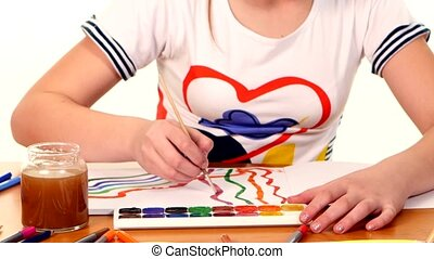 Beautiful girl in varicolored shirt paints color a picture on white background
