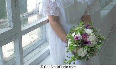 Beautiful girl in vintage white dress sitting on windowsill ond smeling flowers, slow motion