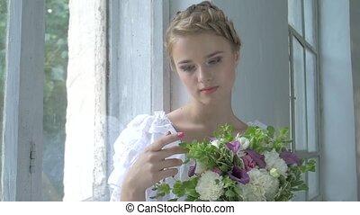 Beautiful girl in vintage white dress sitting on windowsill ond touching flowers, slow motion