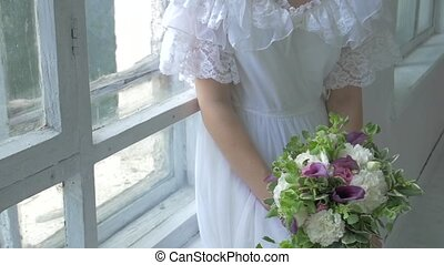 Beautiful girl in vintage white dress sitting on windowsill ond watching throw the window, slow motion