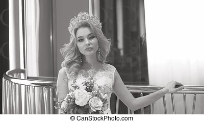 Beautiful girl in wedding dress posing for a photographer, black and white frame