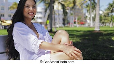 Beautiful girl in white dress on bench in park - Charming...